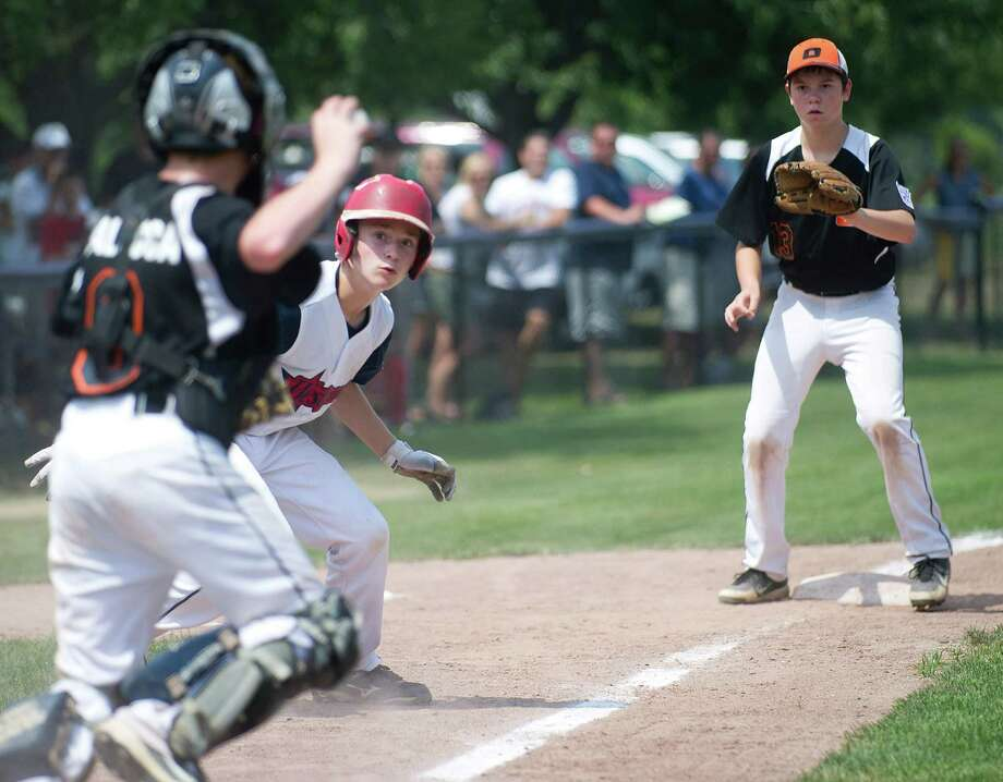 Westport's Harry Azadian is caught between Orange's catcher Jack Balocca and third baseman Mike Ficaro during Saturday's Little League Section 1 tournament game at Frank Noto Field in West Beach Park in Stamford, Conn., on July 20, 2013. Photo: Lindsay Perry / Stamford Advocate