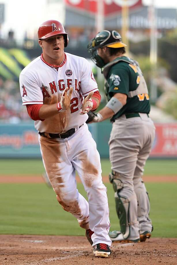 ANAHEIM, CA - JULY 20:  Mike Trout #27 of the Los Angeles Angels reacts to his run after scoring on a sacrifice fly from Josh Hamilton #32 in front of Derek Norris #36 of the Oakland Athletics for a 1-0 lead during the first inning at Angel Stadium of Anaheim on July 20, 2013 in Anaheim, California.  (Photo by Harry How/Getty Images) Photo: Harry How, Getty Images