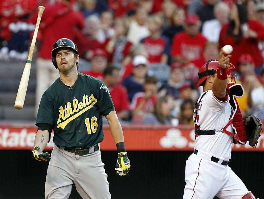 Oakland Athletics' Josh Reddick (16) flips his bat after striking out as Los Angeles Angels catcher Hank Conger, right, throws to the third baseman in the fifth inning during a baseball game on Saturday, July 20, 2013, in Anaheim, Calif. (AP Photo/Alex Gallardo) Photo: Alex Gallardo, Associated Press