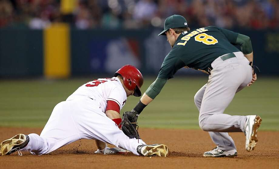 Los Angeles Angels' J.B. Shuck, left, slide in for a double as Oakland Athletics shortstop Jed Lowrie (8) applies the late tag in the seventh inning during a baseball game Saturday, July 20, 2013 in Anaheim, Calif.(AP Photo/Alex Gallardo) Photo: Alex Gallardo, Associated Press