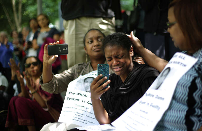 McKenzie Williams, center, becomes emotional during a gathering to protest the killing of Trayvon Martin and the acquittal of George Zimmerman, the man that shot Martin. A few hundred people gathered for a rally at the Federal Courthouse on Stewart and then a march along 5th Avenue. Photographed on Saturday, July 20, 2013.