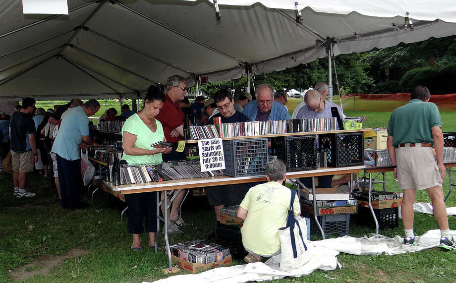 Early-bird shoppers get first crack Saturday at the thousands of books, records, DVDs, video tapes and CDs at the opening of the Westport Library's Summer Book Sale. Photo: Mike Lauterborn / Westport News contributed