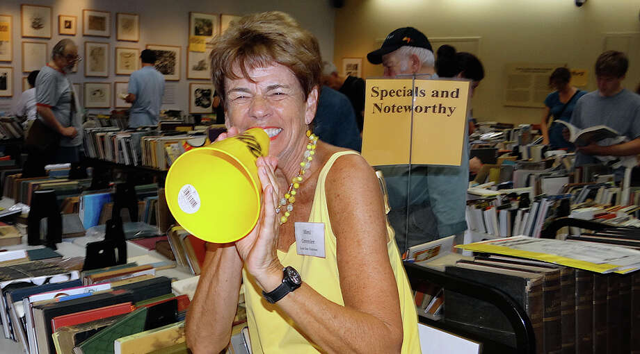 Mimi Greenlee, the chairwoman of Westport Library's Summer Book Sale, clowns with a megaphone as visitors make book selections on the first day of the four-day event Saturday. Photo: Mike Lauterborn / Westport News contributed