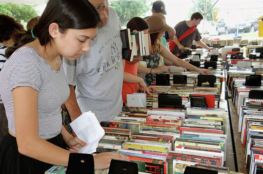 Sophie Ota searches for on her summer AP English reading list Saturday at the first day of the Westport Library's Summer Book Sale. Photo: Mike Lauterborn / Westport News contributed