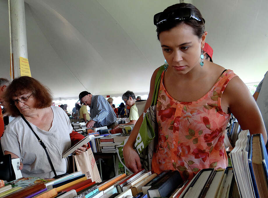 Dana Sharkey of Plainville browses the books on Saturday's opening day of the Westport Library's Summer Book Sale. Photo: Mike Lauterborn / Westport News contributed