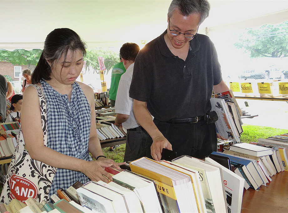 Ellen Saito and Sai Char, of Irvington, N.Y., browse through the stacks of books on Saturday's opening day of Westport Library's Summer Book Sale. Photo: Mike Lauterborn / Westport News contributed