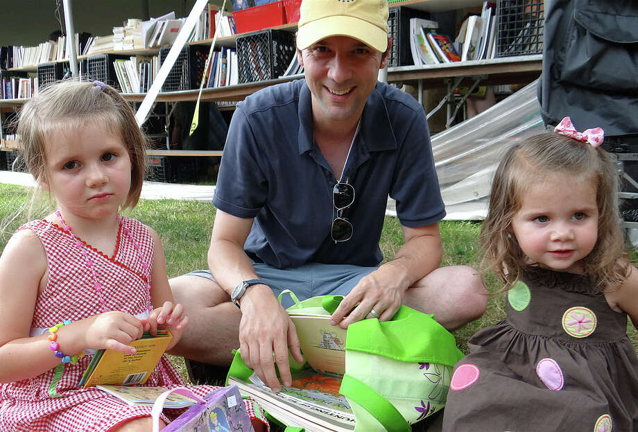Bryan Fisher with daughters Maya and Leila at the Westport Library's Summer Book Sale. Photo: Mike Lauterborn / Westport News contributed