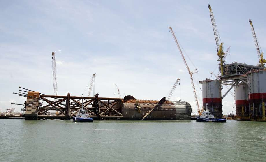 Tugboats are shown beside the Anadarko Petroleum Corporation's Lucius truss spar at Kiewit Offshore Services, 2440 Kiewit Road, Thursday, July 11, 2013, in Ingleside. It is the largest spar built to date by Anadarko. The diameter of the spar is 110 feet and the length is 605 feet. Shown at right is Chevron's tension leg platform named Big Foot. ( Melissa Phillip / Houston Chronicle ) Photo: Melissa Phillip, Houston Chronicle