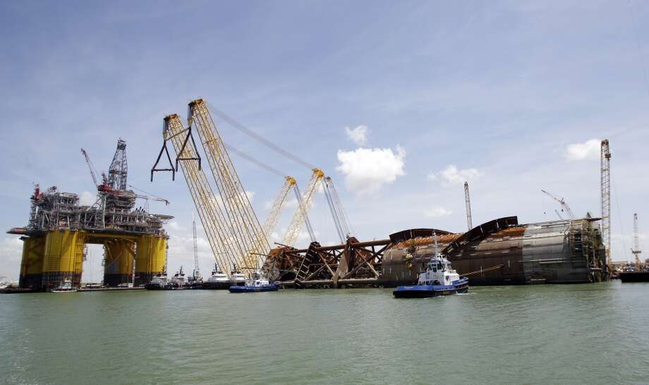 Tugboats are shown beside the Anadarko Petroleum Corporation's Lucius truss spar at Kiewit Offshore Services, 2440 Kiewit Road, Thursday, July 11, 2013, in Ingleside. It is the largest spar built to date by Anadarko. The diameter of the spar is 110 feet and the length is 605 feet. Shown on left is Shell's tension leg platform named Olympus. ( Melissa Phillip / Houston Chronicle ) Photo: Melissa Phillip, Houston Chronicle