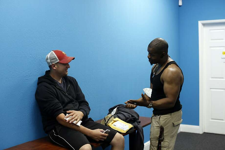 Jose Magdleno, left, and Johnny Ayai, right, talk about getting their tattoos removed in the waiting room before their a tattoo removal treatments at the San Pablo Economic Development Corp. program Removing Barriers in San Pablo, Calif. on July 19, 2013.