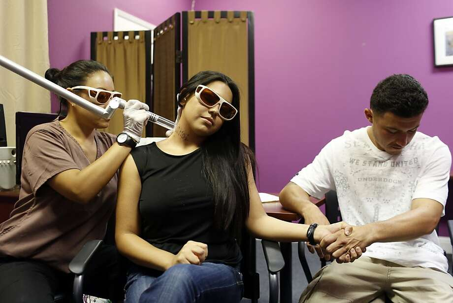 Elizabeth Lopez, center, gets a neck tattoo removed while holding her boyfriend Alejando Curiel's hand during a tattoo removal treatment at the San Pablo Economic Development Corp. program Removing Barriers in San Pablo, Calif. on July 19, 2013.