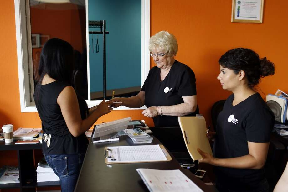 Elizabeth Lopez, left, gets her paperwork processed before a tattoo removal treatment at the San Pablo Economic Development Corp. program Removing Barriers in San Pablo, Calif. on July 19, 2013.