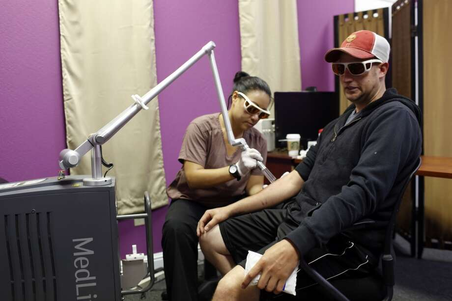 Jose Magdleno, right, gets a tattoo removed by Monarch Laser nurse Christina Chan during a tattoo removal treatment at the San Pablo Economic Development Corp. program Removing Barriers in San Pablo, Calif. on July 19, 2013.