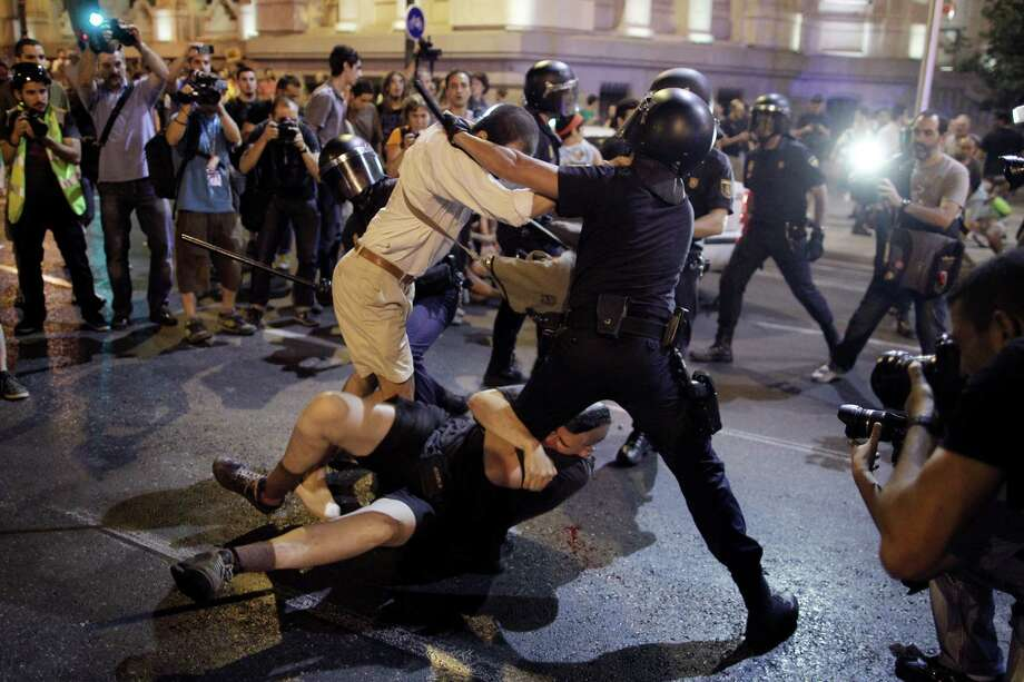 Police clash with protestors during a demonstration against the government in front of the People's Party headquarter in Madrid, Spain, Thursday, July 18, 2013. Spain's Prime Minister on Monday brushed off demands he should resign after text messages emerged showing he had a cozy relationship with a disgraced political party treasurer who amassed 47 million euros ($61 million) in secret Swiss bank accounts. The spectacle of alleged greed and corruption has enraged Spaniards hurting from austerity and sky high unemployment with no end in sight. Photo: AP