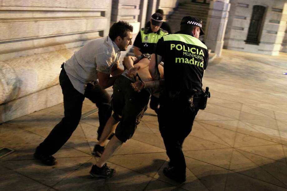 Police arrest a protestor during a demonstration against the government in front of the People's Party headquarters in Madrid, Spain, Thursday, July 18, 2013. Thousands of protesters demanding the resignation of Prime Minister Mariano Rajoy demonstrated Thursday night. Rajoy on Monday brushed off demands he should resign after text messages emerged showing him comforting a former political party treasurer under investigation over a slush fund and secret Swiss bank accounts. The spectacle of alleged greed and corruption has enraged Spaniards hurting from austerity and sky high unemployment. Photo: AP