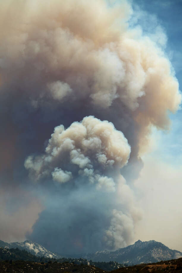 A huge column of smoke rises from the Mountain Fire incident near Idyllwild, Calif., Wednesday, July 17, 2013. Authorities asked for additional evacuations as the wildfire in the mountains southwest of Palm Springs rages on. (AP Photo/The Desert Sun, Richard Lui) Photo: AP