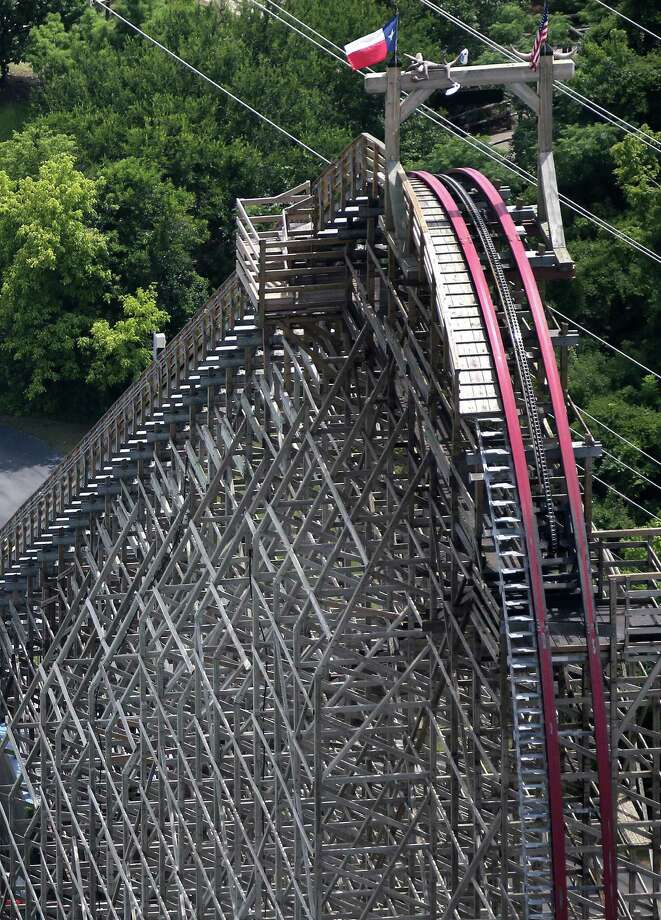 This aerial photo shows the Texas Giant roller coaster at  Six Flags Over Texas where a woman fell to her death, Saturday, July 20, 2013, in Arlington, Texas. Investigators will try to determine if a woman who died while riding the roller coaster at the amusement park Friday night fell from the ride after some witnesses said she wasn't properly secured. (AP Photo/The Dallas Morning News, Louis DeLuca)  Photo: AP