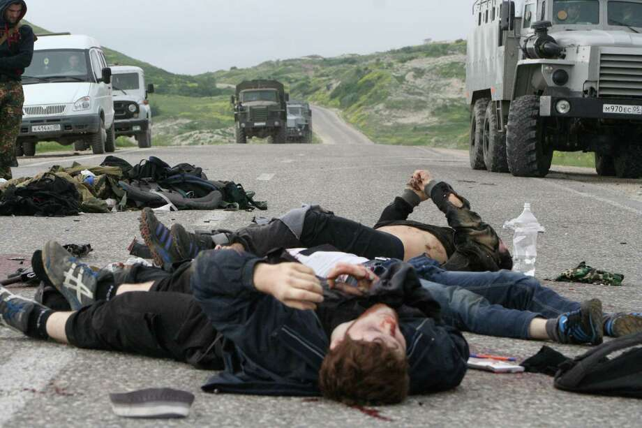 "In this Thursday, May 9, 2013 file photo, bodies of killed militants lie on a highway at Gubden, in Russian republic of Dagestan. The leader of a restive province in Russia's Caucasus Mountains said that local Islamic militants are fighting alongside Syrian rebels and could further destabilize their home region when they come back. Ramazan Abdulatipov, the acting president of the province of Dagestan, urged local authorities on Sunday, July 21, 2013 to prevent the ""export of extremists,"" and make it hard for militants to leave Russia. Photo: AP"