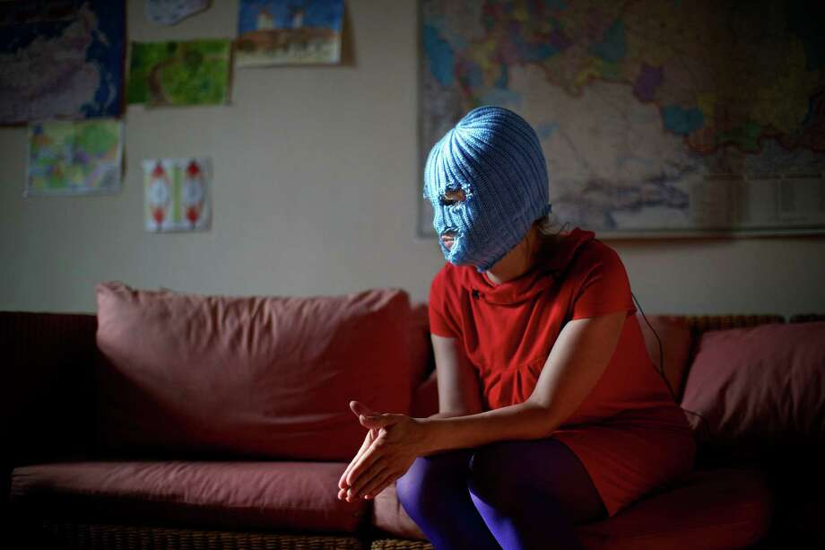 "A member of Russian punk band Pussy Riot, who gave only her stage name of Grelka, wears a blue balaclava as speaks to the media in Moscow, Tuesday, July 16, 2013. Russian provocateurs Pussy Riot are back in action, releasing their first music video since three members went to prison last year for a prank denouncing Vladimir Putin. The video shows band members in trademark bright-colored balaclavas and short skirts, cavorting and shrieking atop an oil rig. Backed by hectic guitar and a drum fusillade, they pour oil on a large photo of state oil giant Rosneft's chairman and liken Putin to an Iranian ayatollah. Pussy Riot member Grelka said after the video's Tuesday release that ""the main message is that Putin has spread the country's wealth among his friends."" Photo: AP"