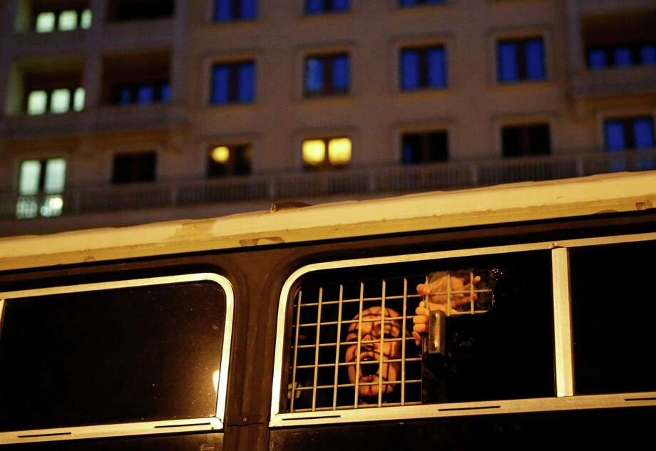 A detained protestor looks through a window of a police track as people gather in support of opposition figure Alexei Navalny, in the center of Moscow, Russia, Thursday, July 18, 2013. Navalny was convicted of embezzlement Thursday and sentenced to five years in prison, a harsh ruling his supporters called an obvious attempt to shut down a top foe of President Vladimir Putin and intimidate other opposition activists. Photo: AP