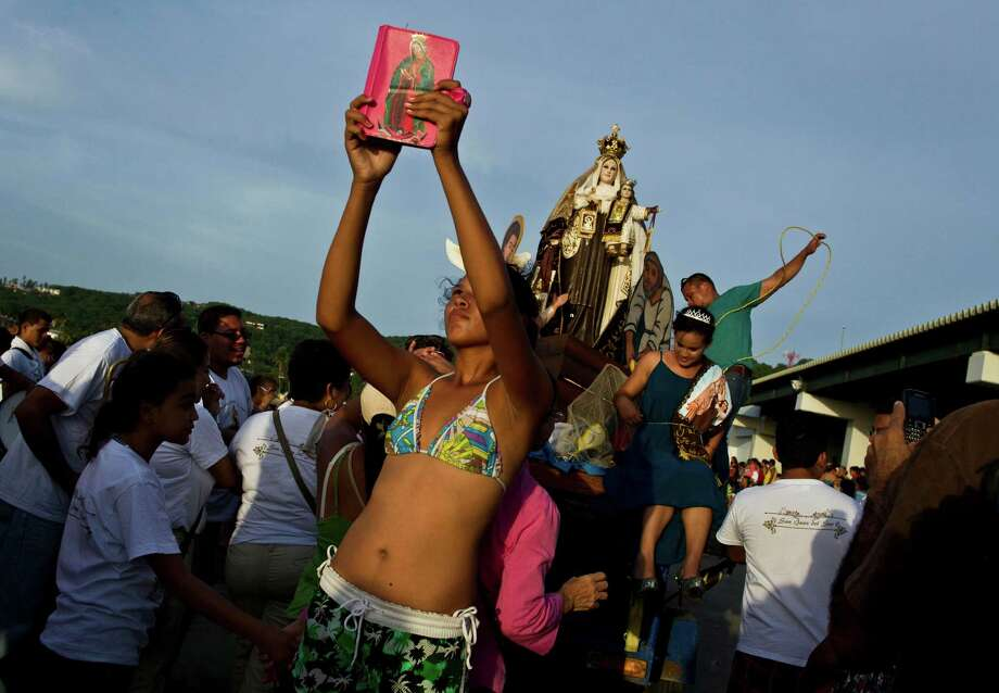A young woman takes a picture with her tablet which is decorated by an image of the Virgin of Guadalupe during a religious procession of the Virgin of Carmen on the shores of the Pacific Ocean in San Juan del Sur, Nicaragua, Tuesday, July 16, 2013. Nicaragua's fishing community celebrate the feast day of the Virgin Carmen who is worshipped by Catholics as the patron saint of fishermen and sailors. Photo: AP