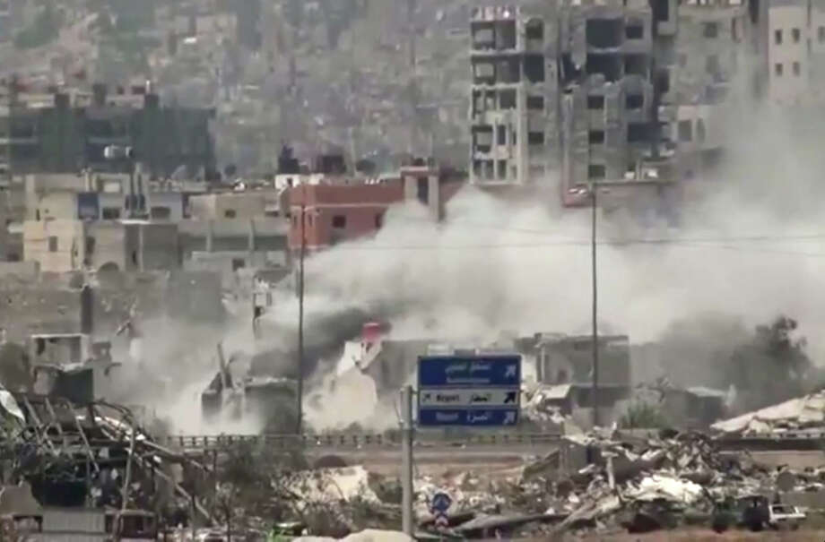 In this image taken from video obtained from Ugarit News, which has been authenticated based on its contents and other AP reporting, shows shelling of the Al-Qaboun neighborhood in rural Damascus, Syria, Monday, July 15, 2013. After seizing the momentum in recent months in Syria's civil war, President Bashar Assad's forces are on the offensive against the rebels on several fronts, including in Idlib province along the border with Turkey. Government forces are in firm control of the provincial capital of same name, while dozens of rebel brigades control the countryside. Photo: AP