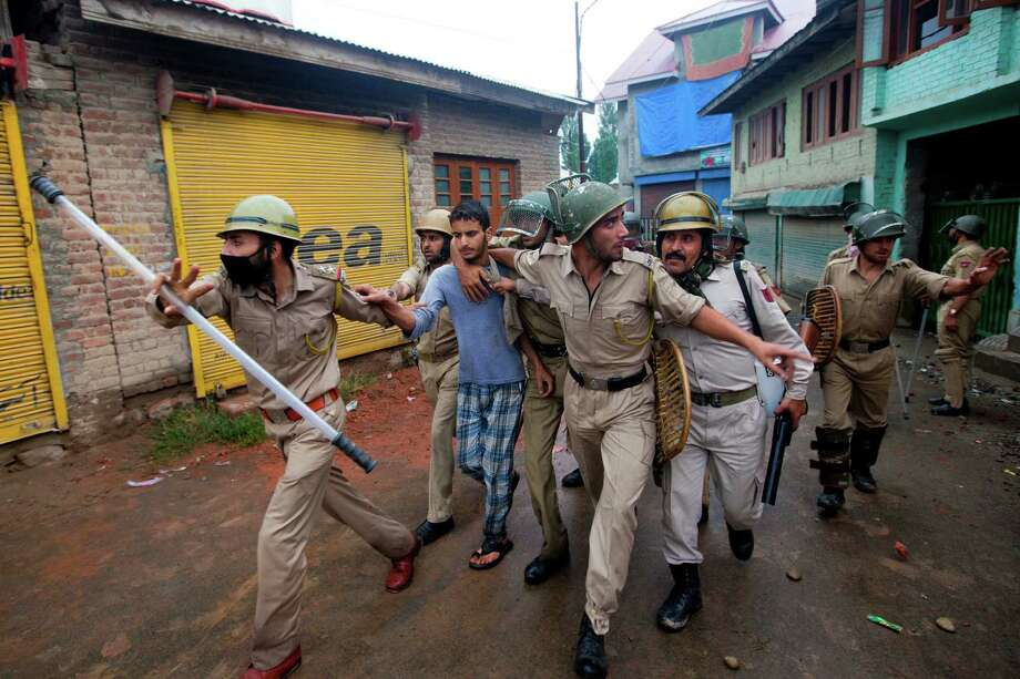 Indian police officer arrest a Kashmiri youth protesting during curfew in Srinagar, India, Saturday, July 20, 2013. Authorities in Indian-administered Kashmir Saturday decided to extend a curfew following violent protests over the deaths of four people in shooting by the paramilitary police. Although the situation remained largely peaceful on Saturday, clashes between stone-throwing mobs and security forces until late Friday left 59 people, including 49 police and paramilitary, injured, a police spokesman said. Photo: AP
