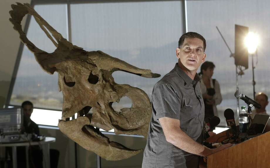 "Dinosaur paleontologist Scott Sampson, is shown making remarks as he stands next to a reconstruction of a ""Nasutoceratops titusi"" during a news conference at the Natural History Museum of Utah Wednesday, July 17, 2013, in Salt lake City.   The dinosaur was a wide-bodied plant-eater that grew to 15 feet long and weighed 2 1/2 tons. It's unique for its oversized nose and exceptionally long, forward-pointing curved horns over the eyes. It's part of the same family as the well-known Triceratops. Photo: AP"