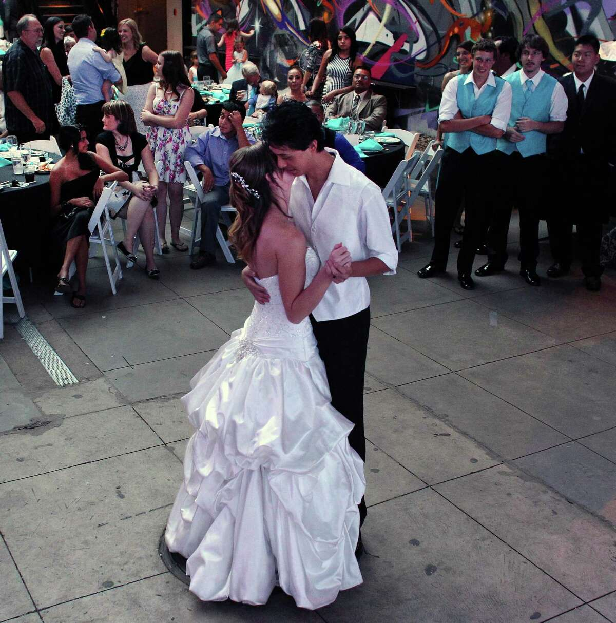 Aurora shooting survivors - and now newlyweds - Kirstin and Eugene Han perform the ceremonial first dance during their wedding reception, in Denver, Saturday July 20, 2013. One year to the day since Eugene was shot while trying to protect his longtime girlfriend Kirstin - then Kirstin Davis - from harm during a shooting rampage in an Aurora theater, the two have become man and wife.