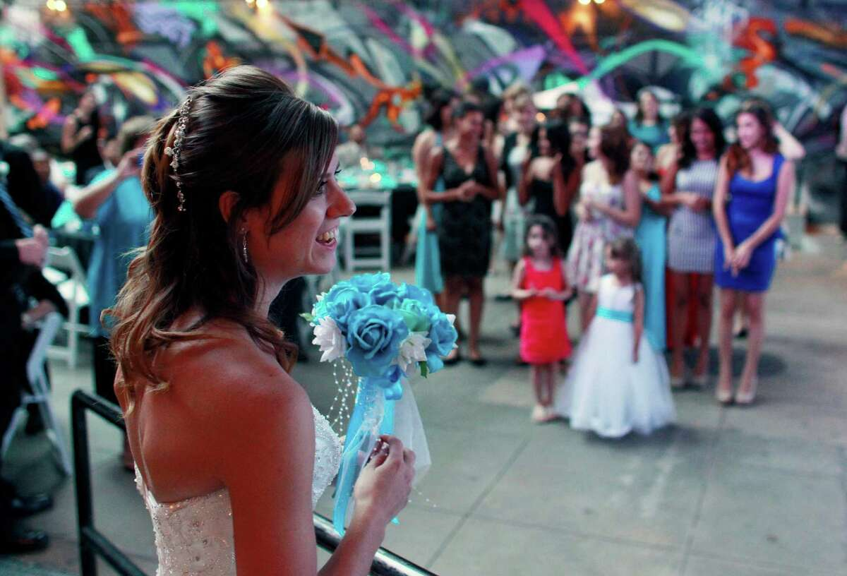 Aurora shooting survivor - and now newlywed - Kirstin Han prepares to throw her bouquet during the wedding reception for her and her husband Eugene Han, in Denver, Saturday July 20, 2013. One year to the day since Eugene was shot while trying to protect his longtime girlfriend Kirstin - then Kirstin Davis - from harm during a shooting rampage in an Aurora theater, the two have become man and wife.