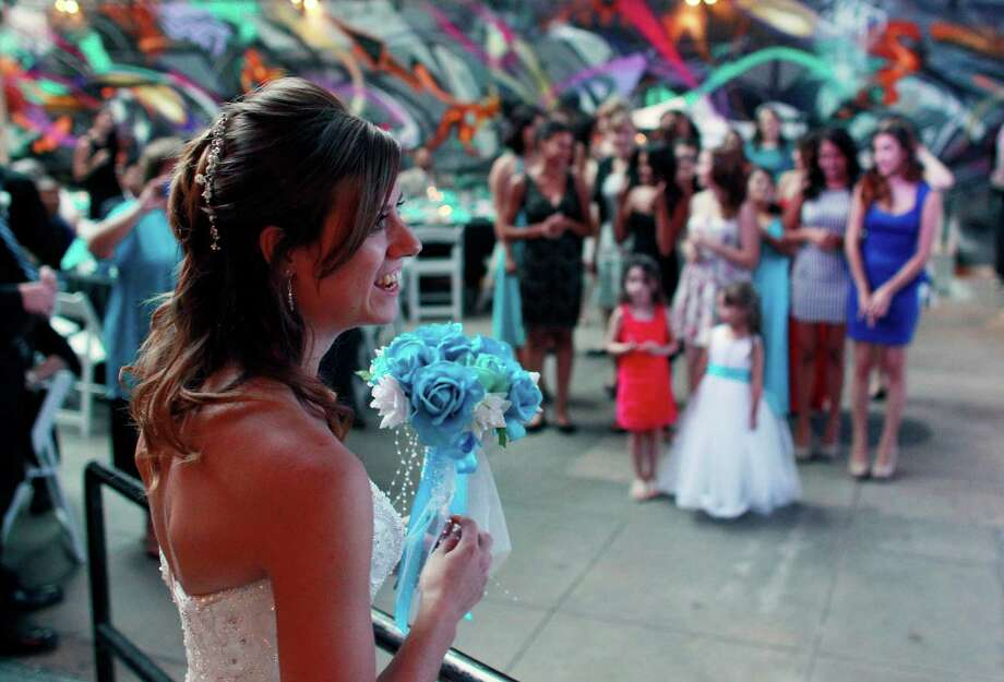 Aurora shooting survivor - and now newlywed - Kirstin Han prepares to throw her bouquet during the wedding reception for her and her husband Eugene Han, in Denver, Saturday July 20, 2013. One year to the day since Eugene was shot while trying to protect his longtime girlfriend Kirstin - then Kirstin Davis - from harm during a shooting rampage in an Aurora theater, the two have become man and wife. Photo: AP