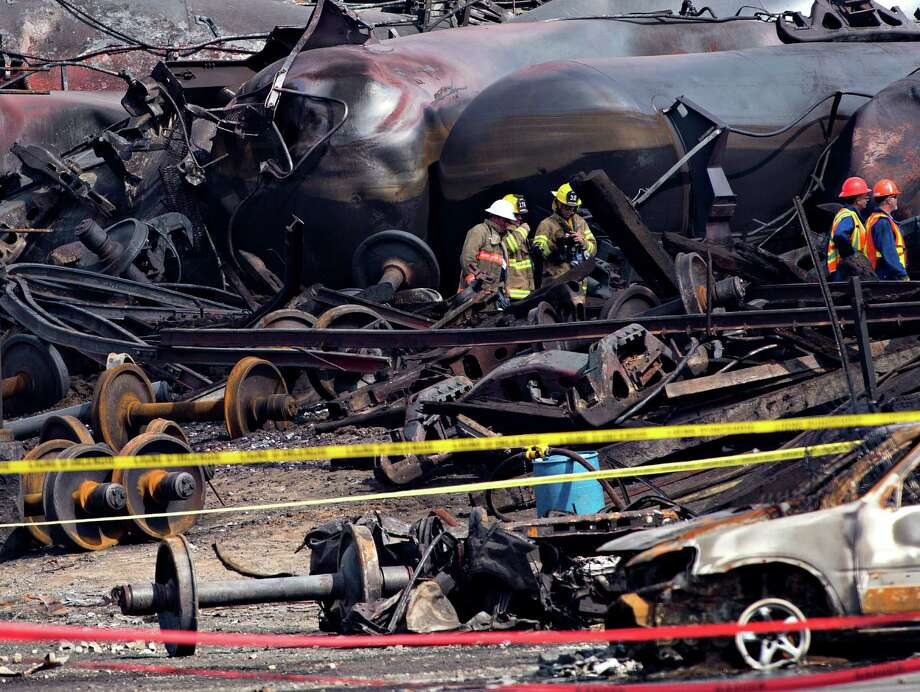 Crews move through the debris Tuesday, July 16, 2013, as work continues at the crash site of the train derailment and fire in Lac-Megantic, Quebec.  The July 6, 2013 derailment left 37 people confirmed dead and another 13 missing and presumed dead. Photo: AP