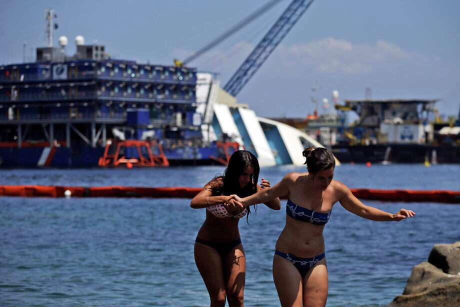 Sunbathers walk on rocks as the Costa Concordia cruiser is visible in background, in the Tuscan Island of Isola del Giglio, Monday, July 15, 2013. Salvage crews are working against time to right and remove the shipwrecked Costa Concordia cruise ship, which is steadily compressing down on itself from sheer weight onto its granite seabed perch off the Tuscan island of Giglio. Salvage master Nick Sloane said Monday that the Concordia has compressed some 3 meters (10 feet) since it came to rest on the rocks Jan. 13, 2012 after ramming a jagged reef during a stunt ordered by the captain that cost the lives of 32 people. Photo: AP