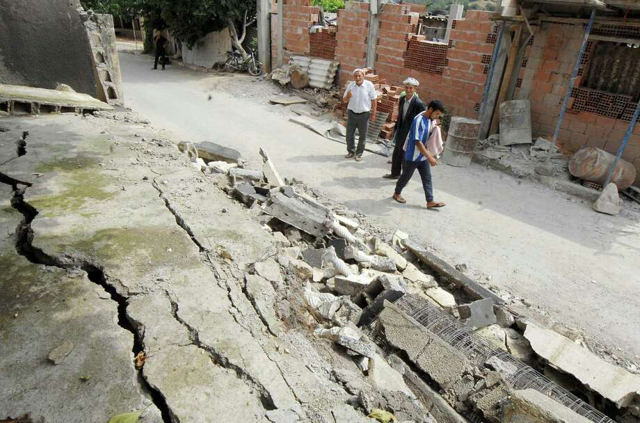 Residents walk in a damaged street after a quake hit Hamam Melounane, near Blida, Algeria, early Wednesday, July 17, 2013. A magnitude 5.1 earthquake hit an area south of the Algerian capital, injuring more than 10 people and causing minor damage to buildings. Photo: AP