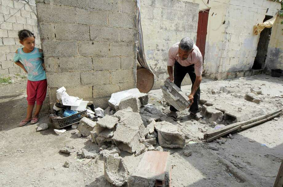 A man removes rubble after a quake hit Hamam Melounane, near Blida, Algeria, early Wednesday, July 17, 2013. A magnitude 5.1 earthquake hit an area south of the Algerian capital, injuring more than 10 people and causing minor damage to buildings. Photo: AP
