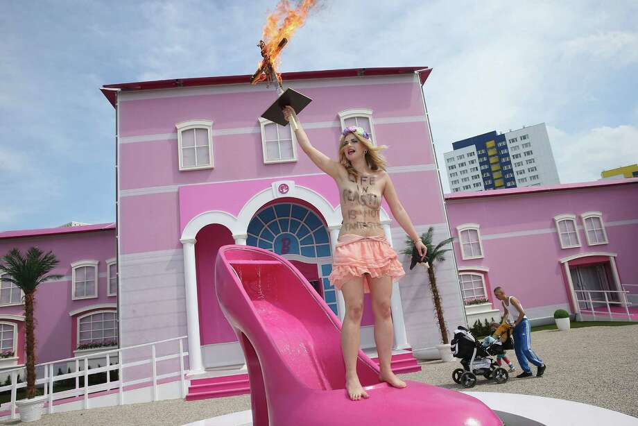 "A bare-breasted FEMEN protester with an inscription on her body that reads: ""Life In Plastic Is Not Fantastic"" yells protest slogans while holding up a burning cross with a Barbie doll attached to it outside the Barbie Dreamhouse Experience on May 16, 2013 in Berlin, Germany. The Barbie Dreamhouse is a life-sized house full of Barbie fashion, furniture and accessories and will be open to the public until August 25 before it moves on to other cities in Europe. Photo: Sean Gallup, Getty Images / 2013 Getty Images"