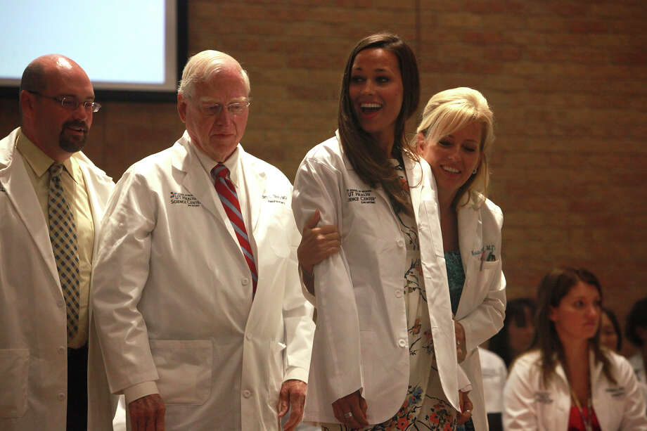 Heidi Held receives her white coat from her grandfather, Dr. Jim Story, and her mother, Dr. Kristen Held at the Holly Auditorium, UT Health Science Center at San Antonio on Sunday, July 21, 2013. About a thousand friends, family, and alumni were in attendance for the ceremony. Photo: Abbey Oldham, San Antonio Express-News / © San Antonio Express-News