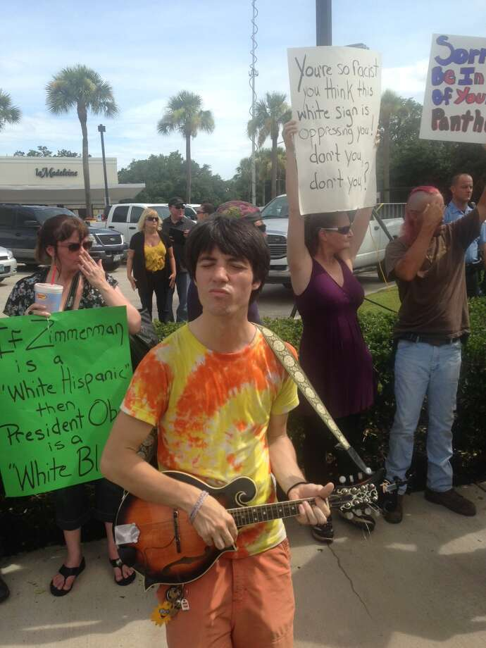 Cameron Belcher plays a mandoline at protest.