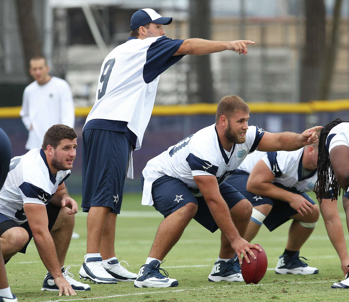 Rookie center Travis Frederick (center) joins quarterback Tony Romo over the ball at the Dallas Cowboys training camp on Sunday, July 21, 2013 in Oxnard.