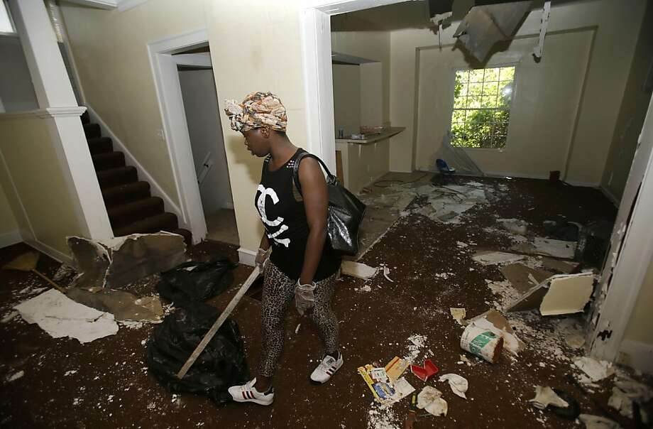 Volunteer Sanautica Hicks-Ross searches a vacant home in the area where three bodies were found. Photo: Tony Dejak, Associated Press