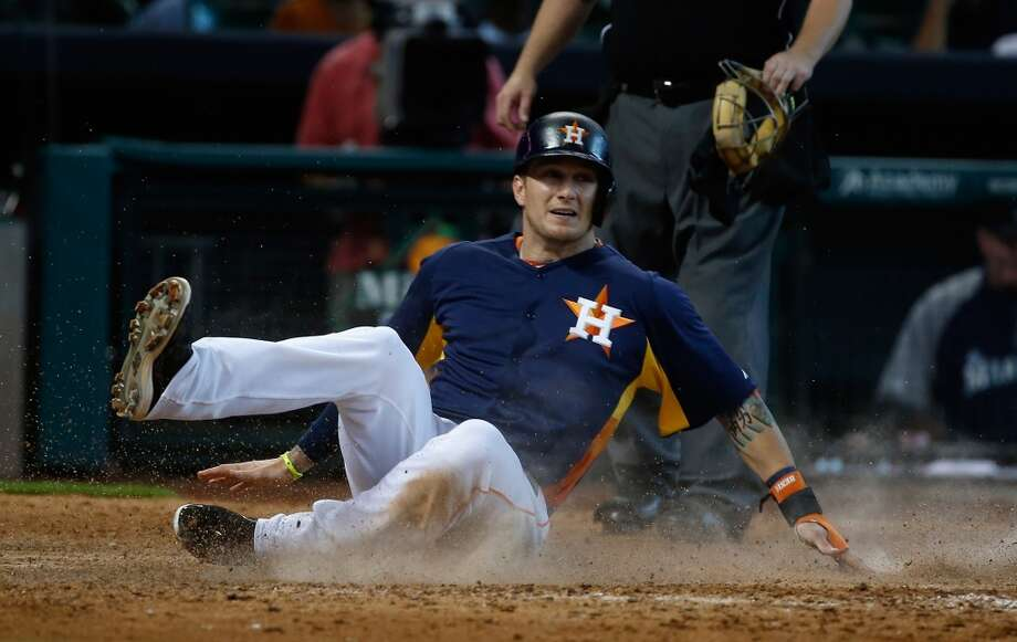 Brandon Barnes of the Astros slides into home safely to score a run.
