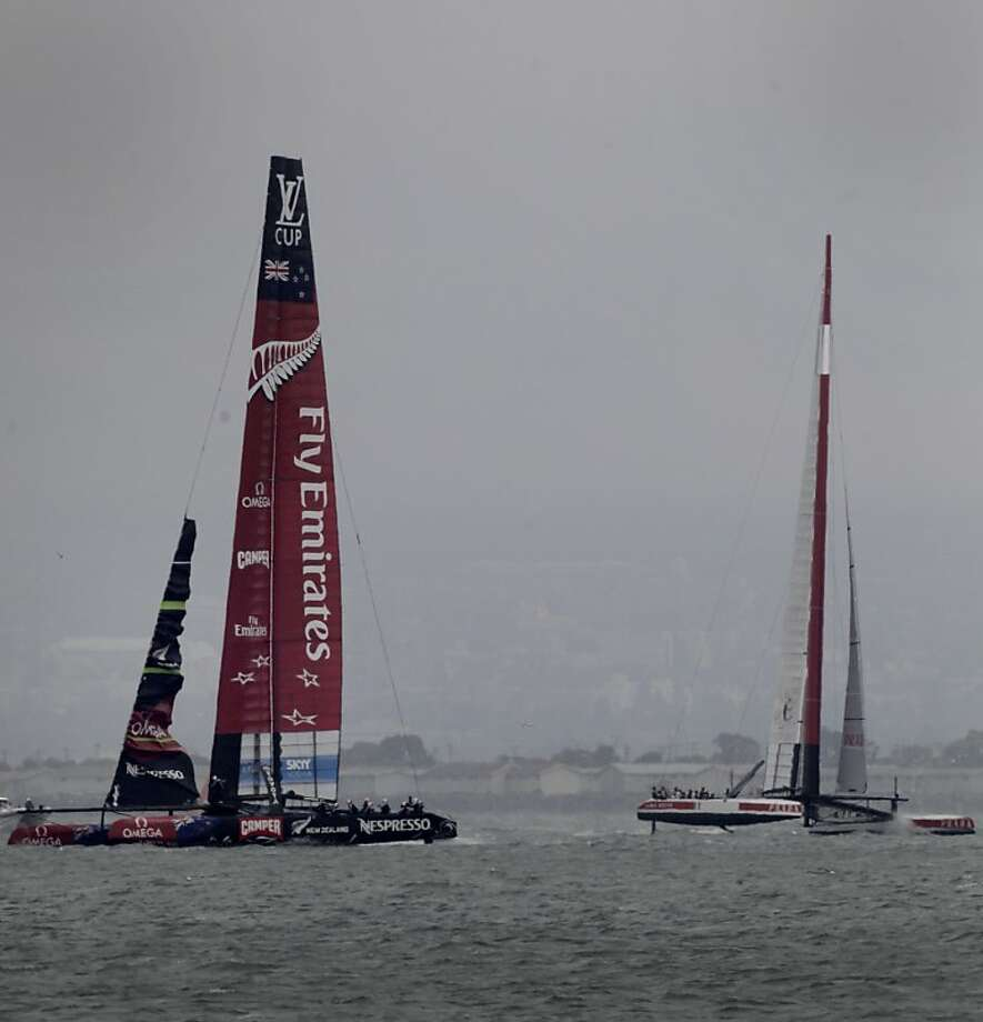 Sailing with a broken jib (front) sail, the Emirates New Zealand catamaran (left) leads the Italian boat en route to winning by 2 minutes and 19 seconds to clinch the round-robin phase of the challenger series. Photo: Brant Ward, The Chronicle