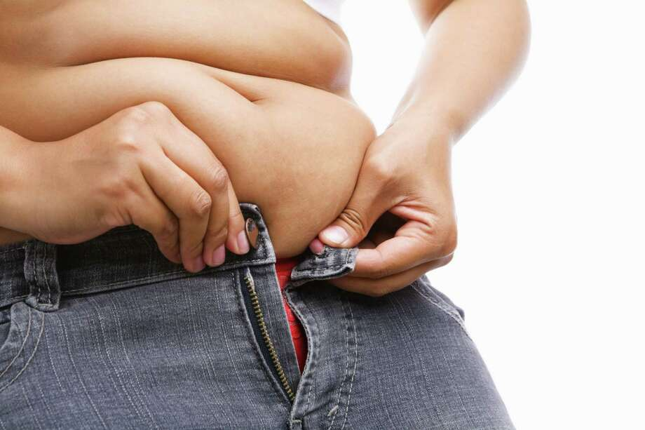 Woman trying hand to zipper her jeans, a concept for obesity issue Photo: Rudyanto Wijaya / Arto - Fotolia