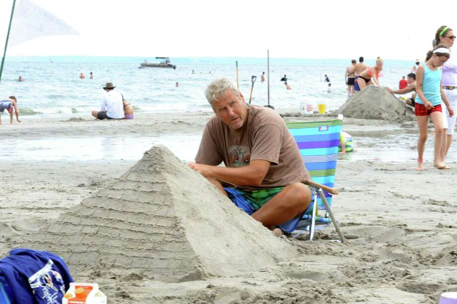 Tom Johnson makes pyramids at Parks and Recreation Department's annual Sand Sculpture Festival in Old Greenwich, Conn., Sunday, July 21, 2013. Photo: Helen Neafsey / Greenwich Time