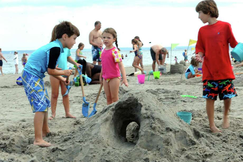 Nathan Jones, 8, his sister, Adriana, 7, and Carolina, 6, and his cousin, Brandon Larossa, 12, making a tunnel at Parks and Recreation Department's annual Sand Sculpture Festival in Greenwich Point beach, Conn., Sunday, July 21, 2013. Photo: Helen Neafsey / Greenwich Time