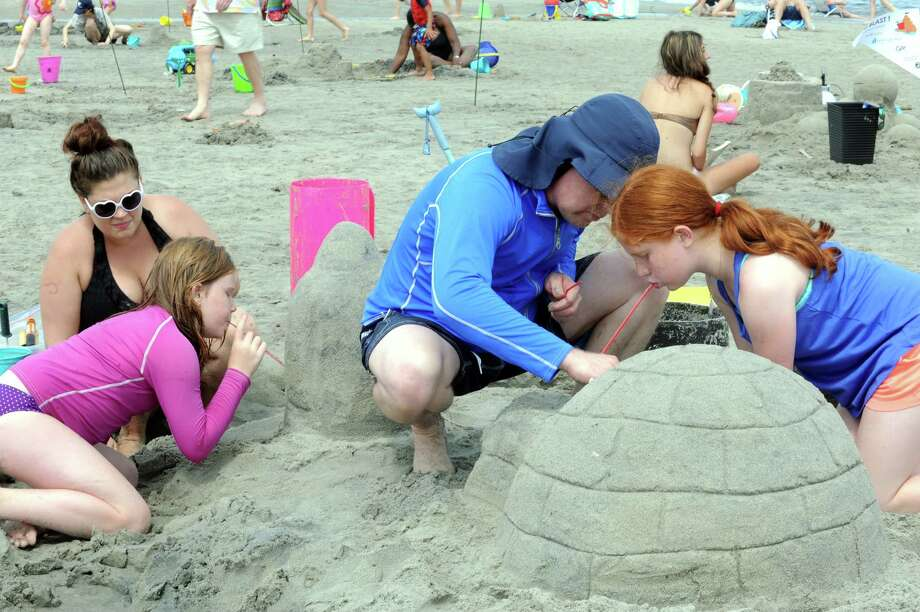 Demetria DeMakes, 9, Melissa Neagles, Darrel DeMakes, and Anastasia,11, makes an Eskimo hut,  a polar bear and her baby in the sand at Parks and Recreation Department's annual Sand Sculpture Festival in Greenwich Point beach, Conn., Sunday, July 21, 2013. Photo: Helen Neafsey / Greenwich Time