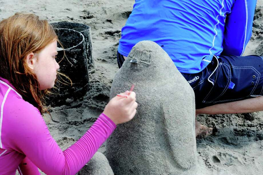 Demetria DeMakes, 9, works on a Polar bear at Parks and Recreation Department's annual Sand Sculpture Festival in Greenwich Point beach, Conn., Sunday, July 21, 2013. Photo: Helen Neafsey / Greenwich Time
