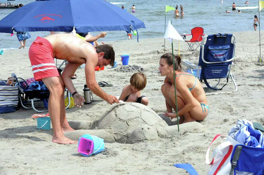 Alejandor Matoso, with his son, Nico, 5, and his wife, Cecilia making a turtle at Parks and Recreation Department's annual Sand Sculpture Festival in Greenwich Point beach, Conn., Sunday, July 21, 2013. Photo: Helen Neafsey / Greenwich Time