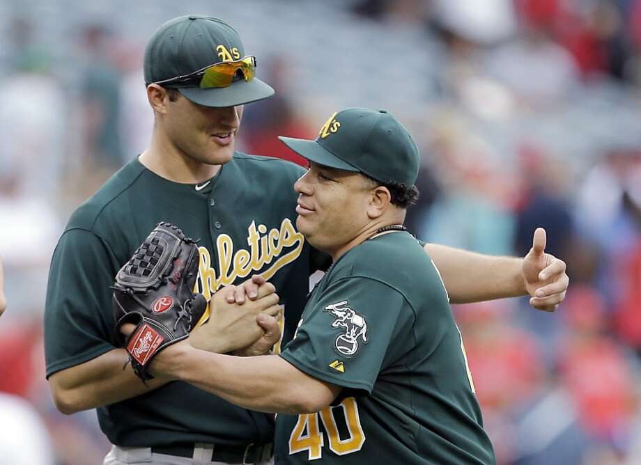 Oakland Athletics pitcher Bartolo Colon, right, celebrates with teammate Nate Freiman after getting a 6-0 complete-game baseball shutout of the Los Angeles Angels in Anaheim, Calif., Sunday, July 21, 2013. (AP Photo/Reed Saxon) Photo: Reed Saxon, Associated Press