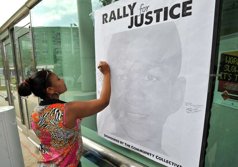 Marie Jean Baptiste writes a few words in remembrance to Trayvon Martin during a Rally for Justice organized by The Community Collective in front of the Stamford Government Center on Sunday, July 21, 2013. Photo: Jason Rearick / Stamford Advocate